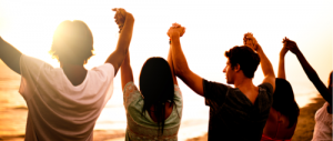 Young people holding hands up in the air