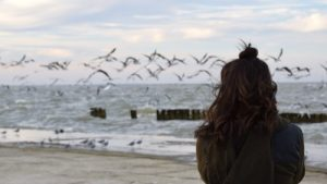Young woman in solitude looking over the ocean